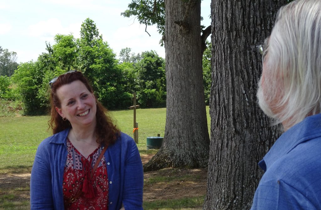 Sara is seen on the left smiling, appearing to be in a conversation with a man. The back of head and body is in the right side of the photograph. They are surrounded by trees and a field.